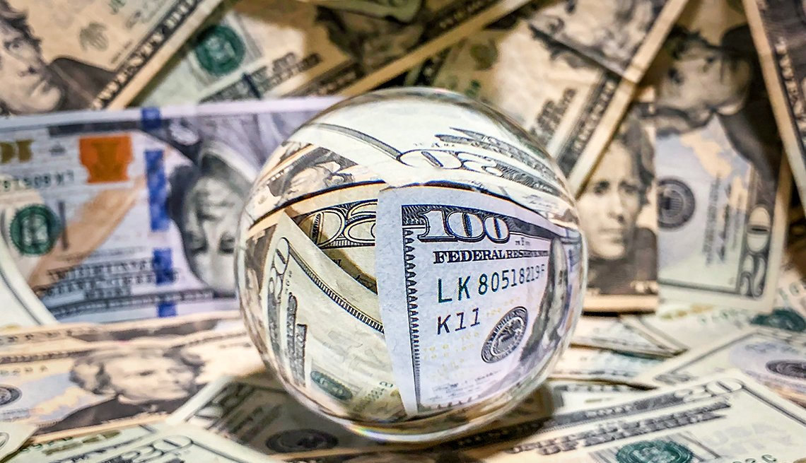A reflective  surface crystal ball surrounded by money