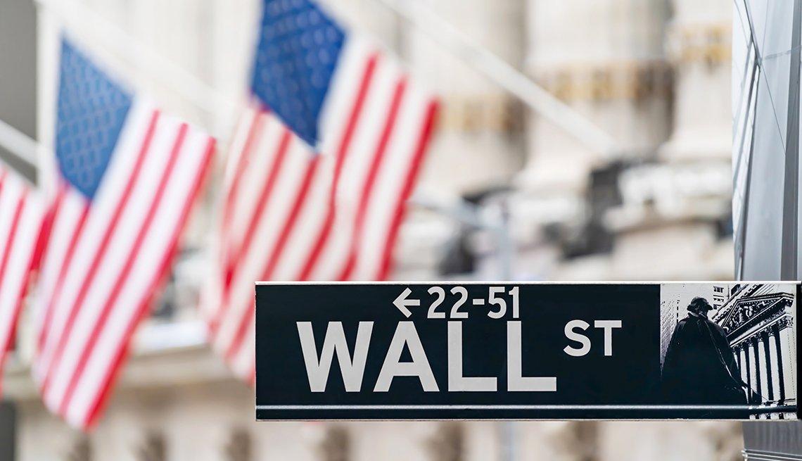 Señal de la calle Wall, en el centro financiero de Nueva York con banderas de Estados Unidos.