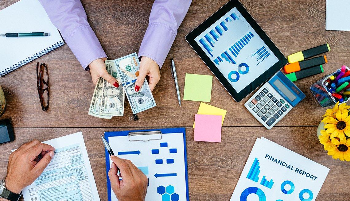Mesa con las manos de dos personas haciendo cuentas, con calculadoras, formularios y dinero.