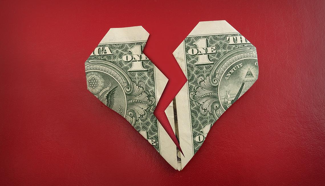 Billete de dólar doblado con estilo de origami en forma de un corazón roto.