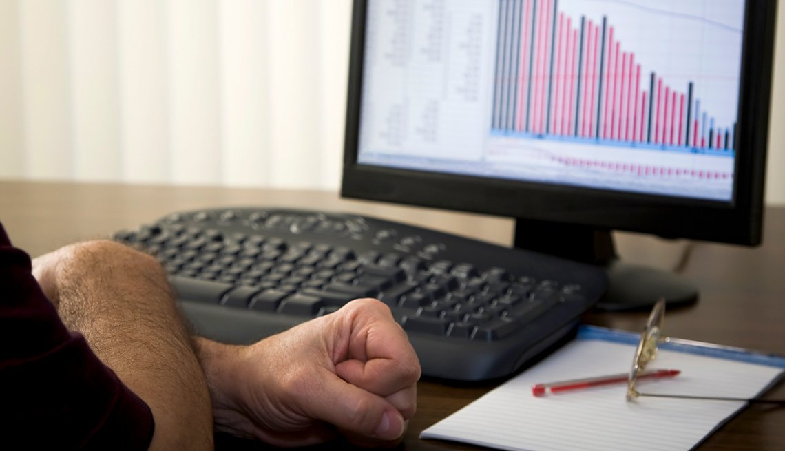 a man clenches his hands in stress while looking at falling stocks on a computer monitor