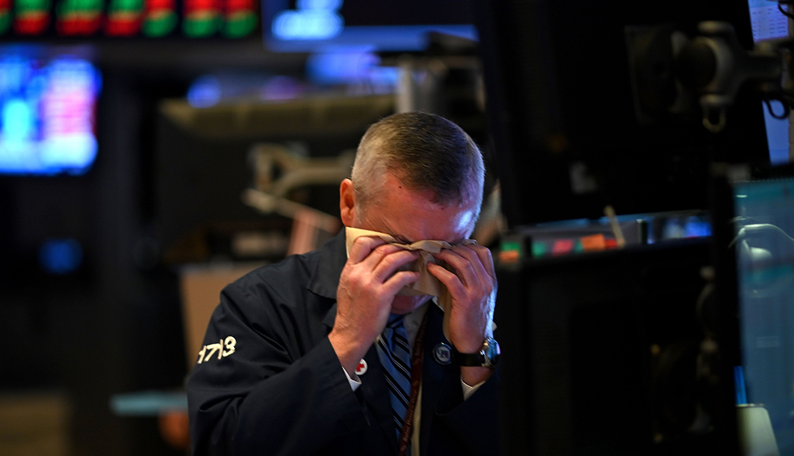A man wipes his face on the floor of the New York Stock Exchange