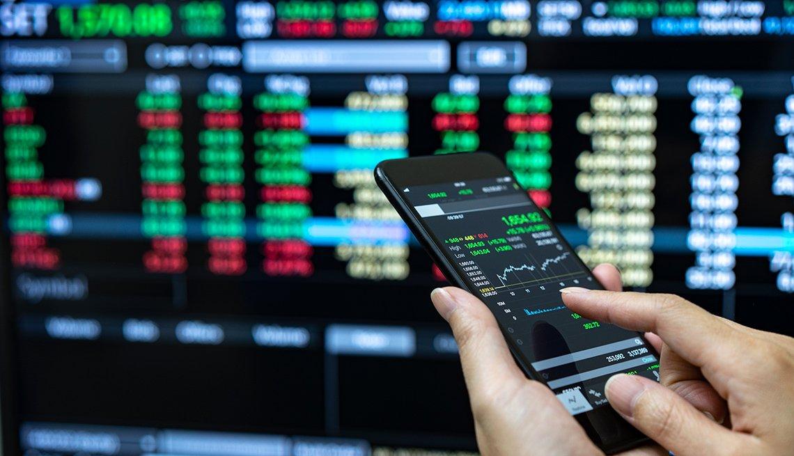 Persona revisando los valores del mercado en un teléfono móvil y al fondo una pantalla con indicadores.