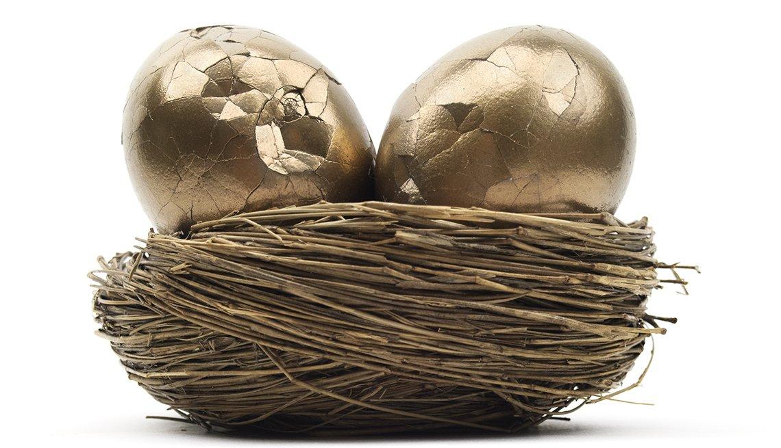 Dos huevos de oro con la cáscara partida encima de un nido.