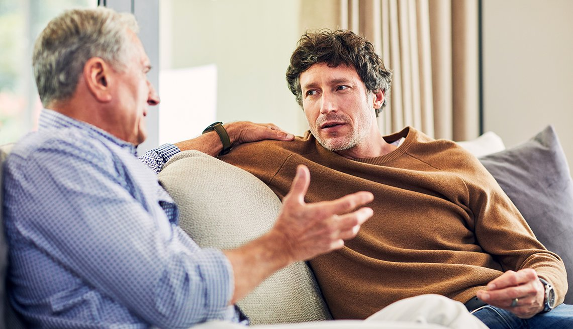 mature man and his senior father with hand on son's shoulder, sitting on the sofa at home and chatting