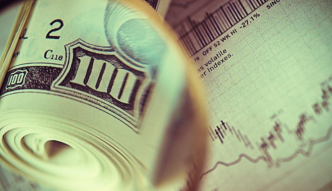 Rollo de billetes de 100 dólares sobre una gráfica del mercado de valores.