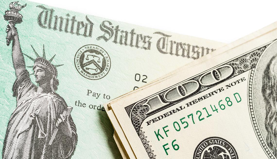 Un cheque del Departamento del Tesoro de Estados Unidos con dinero al lado