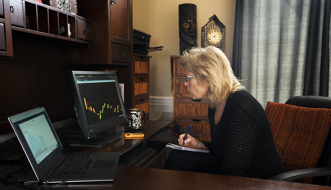 profile of mature woman seated in home office reacting to her sinking portfolio numbers displayed on a graph online due to the coronavirus in 2020