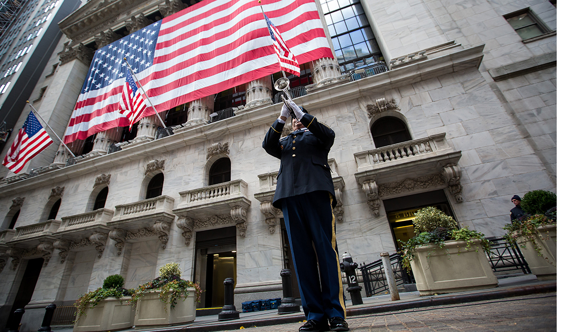 A member of the National Guard plays a trumpet during a flag raising ceremony in honor of Veteran's Day in front of the New York Stock Exchange (NYSE) in New York