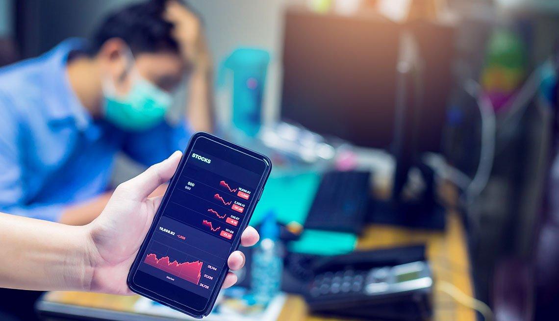 Teléfono móvil con gráficas del mercado de valores y al fondo un inversionista con un tapabocas.