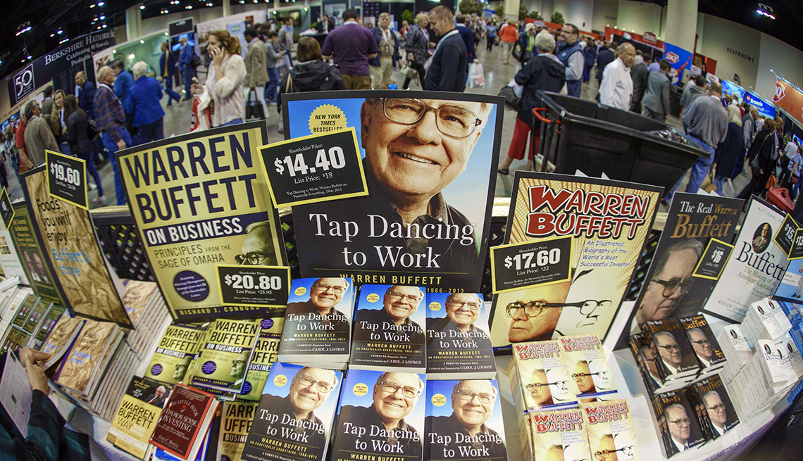 item 5 of Gallery image - fisheye lens view of Berkshire Hathaway shareholders walking past display of Warren Buffett books