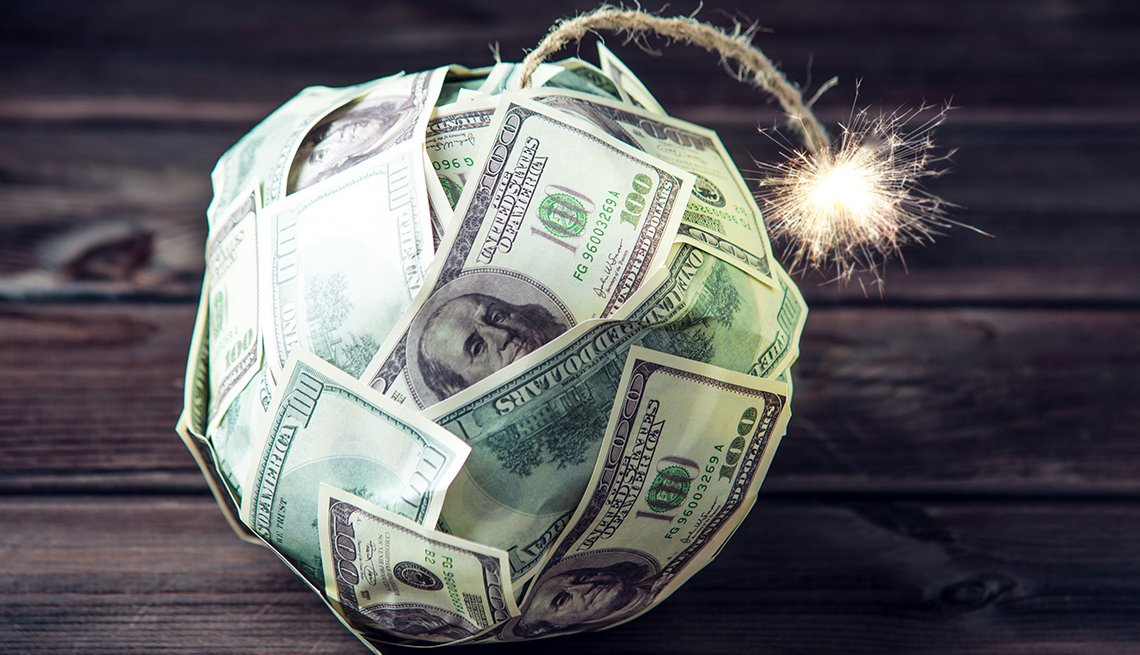 a ball shaped money bomb made out of hundred dollar bills with a lit fuse