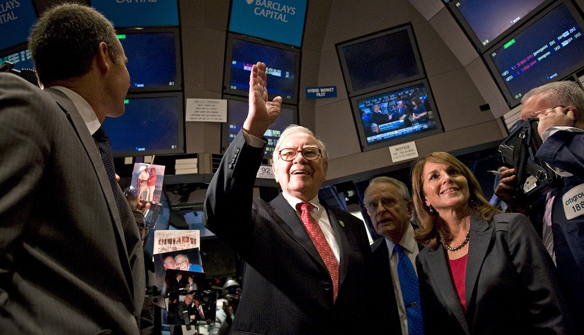 Warren Buffett, chairman and chief executive officer of Berkshire Hathaway Inc., center, waves as he tours floor of the New York Stock Exchange