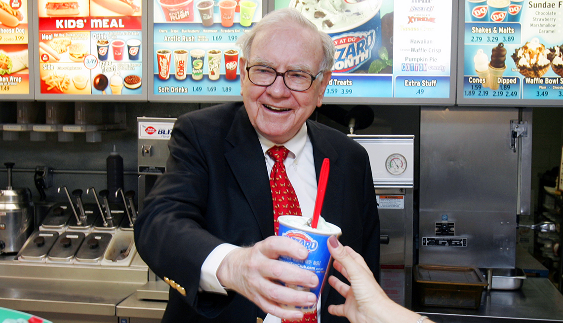 smiling Warren Buffett behind the counter as he hands out a frozen treat at a Dairy Queen in Omaha, Neb.