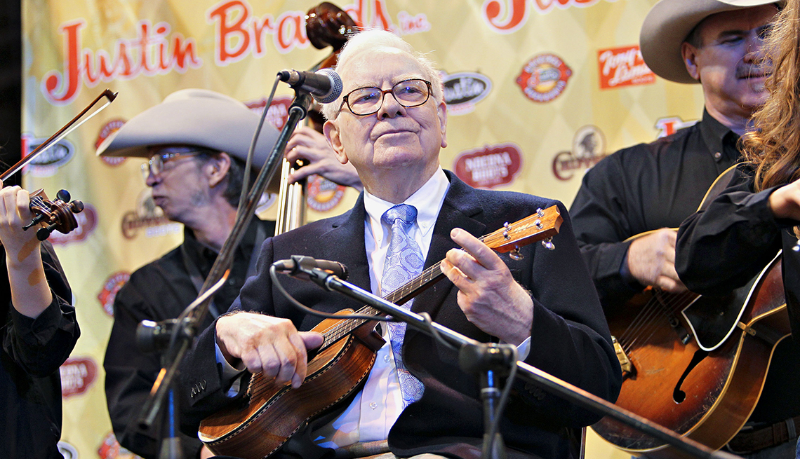 item 9 of Gallery image - Warren Buffett, chief executive officer of Berkshire Hathaway, plays the ukulele during a tour of the exhibition floor prior to a Berkshire Hathaway annual meeting