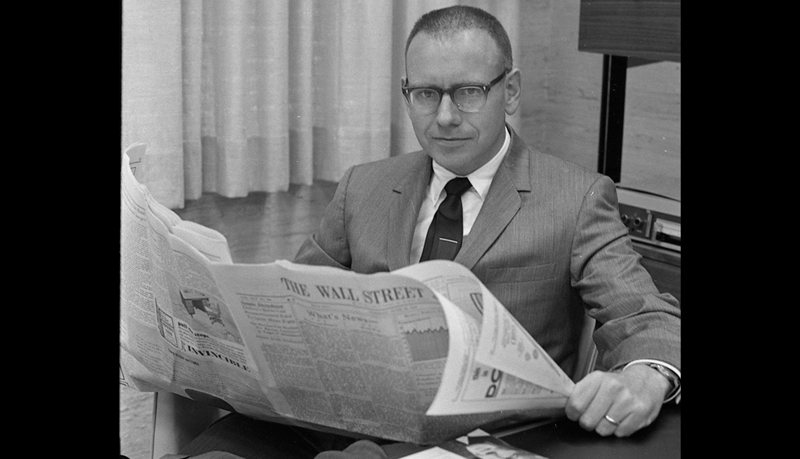 Warren Buffett early in his career sitting at desk and reading the Wall St. Journal