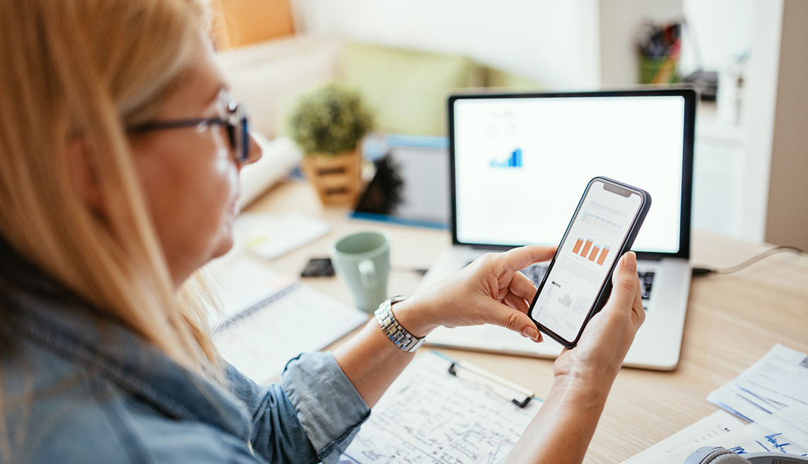 profile of a woman looking at financial charts on a mobile phone with more notes and financial information on desktop and laptop screen