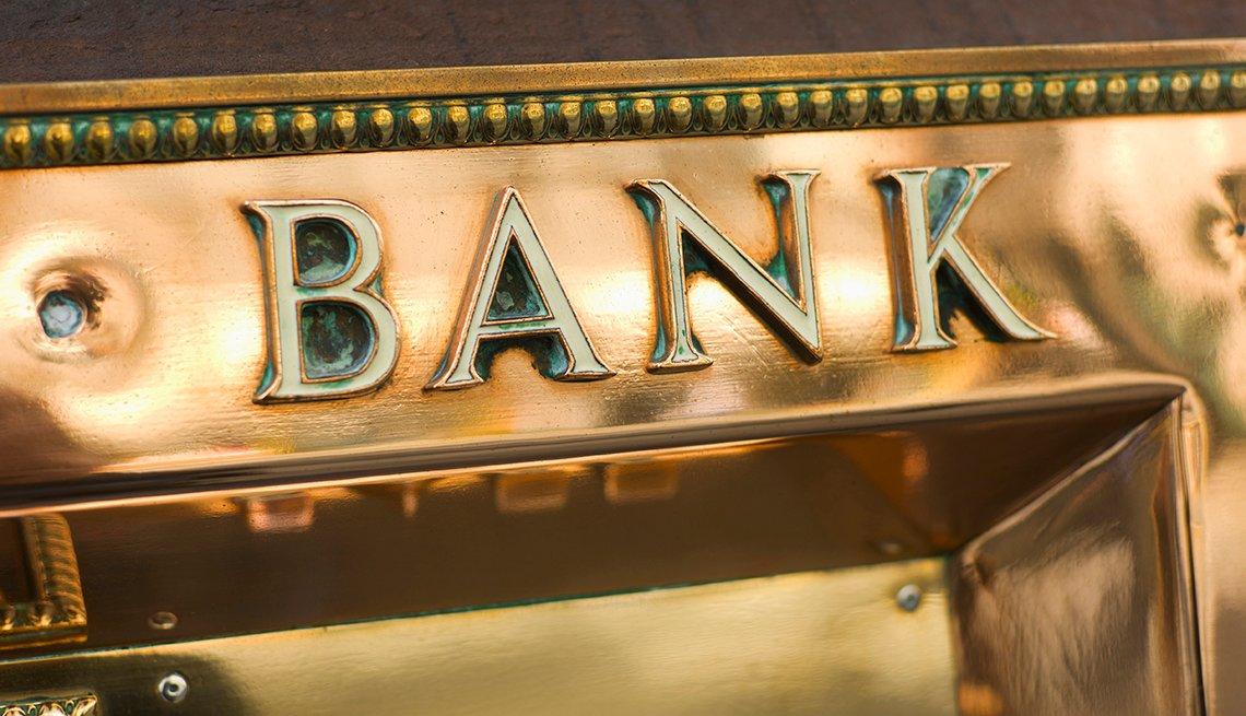 Letrero dorado que dice banco, encima de una puerta de un edificio.