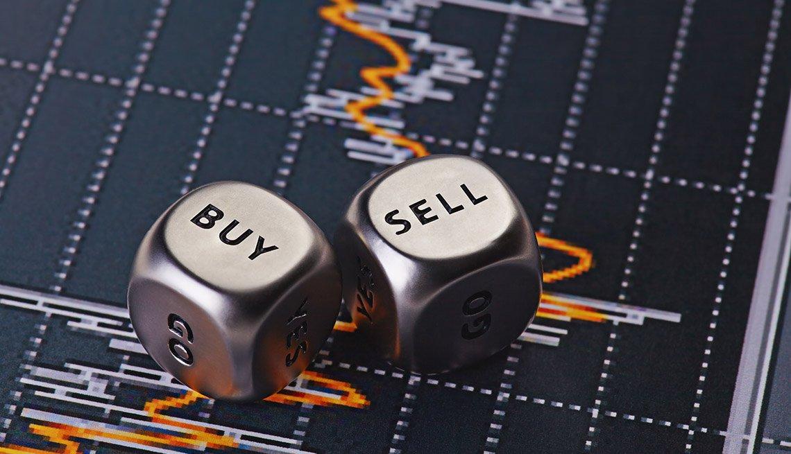 Dados metálicos con las palabras comprar y vender sobre una gráfica estadística del mercado de valores.