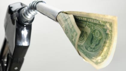 Dólares estadounidenses que salen de una boquilla de una bomba de gas  - ahorrar dinero en gasolina