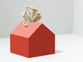 Ways to save on household expenses - Model house moneybox with dollar bills
