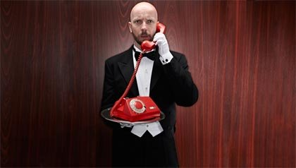 Portero con un telepfone rojo en una bandeja de plata - 15 consejos para lidiar con las llamadas telefónicas no deseadas