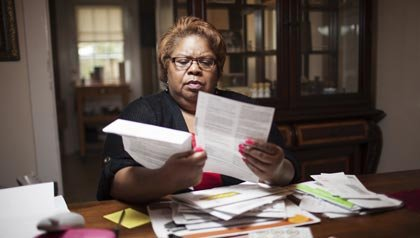 Karen Tucker looks at bills, North Carolina AARP utility training