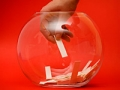 A hand reaches for names in a fishbowl, frugal holiday season ideas