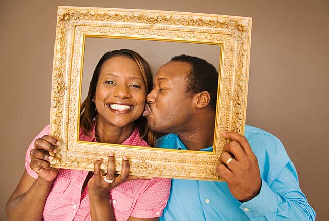 Couple kisses behind picture frame, frugal holiday season