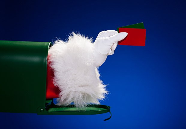 Santa's arm out of a mailbox holding gift card, frugal holiday