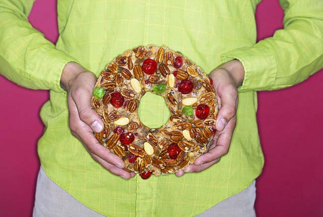 Woman holds a fruitcake against her stomach, frugal holiday