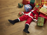 Santa Claus being crushed by holiday gifts.