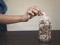 Woman putting coin in savings jar.