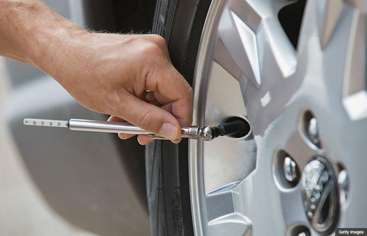 Hombre midiéndole el aire a las gomas de un carro  - Las mejores maneras de gastar $100