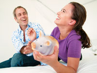 Smiling couple and piggy bank, Jeff Yeager, Married to a cheapskate is beneficial