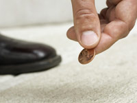 Man picking up penny from street