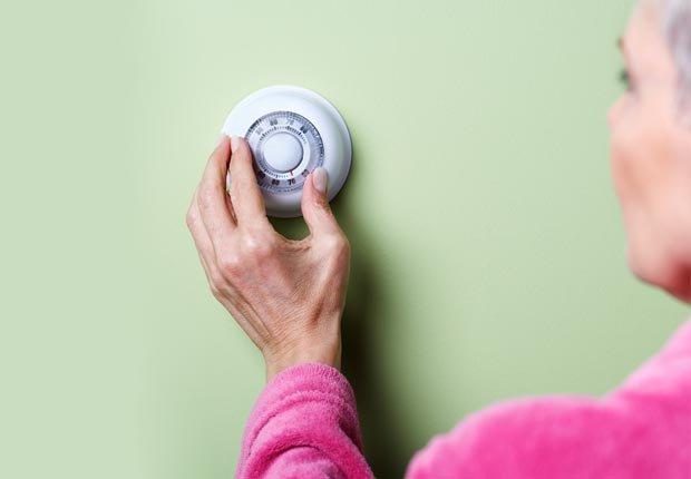 Mujer ajustando un termostato - 8 maneras de enganchar una ganga este verano