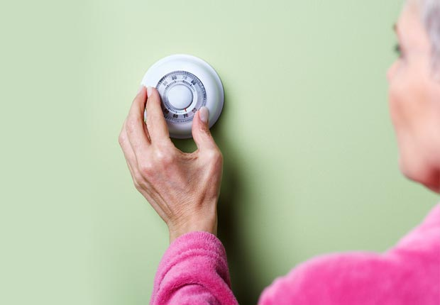 Woman adjusting thermostat (Sean Justice/Corbis)