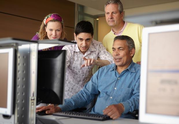 Students gathered around computer in class (Nick White/Corbis)