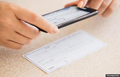 La mano de una mujer que realiza operaciones bancarias en línea con el teléfono móvil, cómo utilizar la Banca en Línea