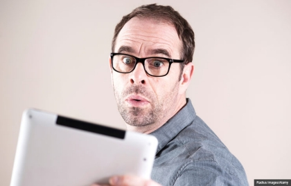 Surprised man with electronic tablet, Protect your personal information after an ended relationship (Radius Images/Alamy)