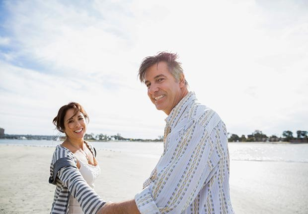 Portrait of smiling mature couple on beach vacation (Hero Images/Getty Images)