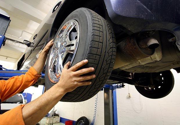Mecánico cambiando una rueda de coche - 10 Productos en donde los cupones te pueden ayudar a ahorrar dinero