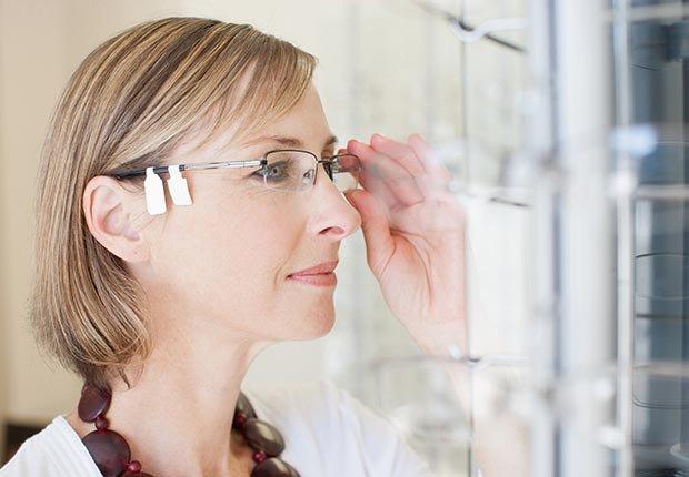 Mujer que intenta en las gafas en la tienda de optómetra - 10 Productos en donde los cupones te pueden ayudar a ahorrar dinero