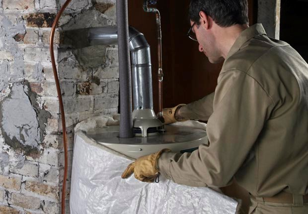 Worker Installing Hot Water Heater Blanket