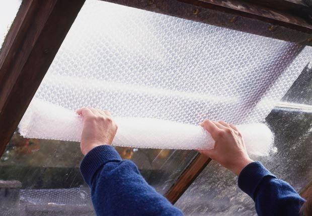 Aislar ventanas del sótano con plástico de burbujas - 10 mejoras para el hogar por menos de $100