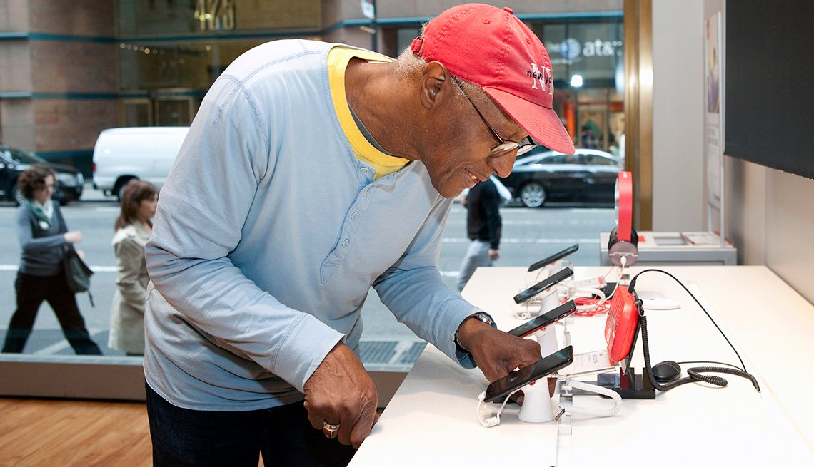 Richard Swarm, viendo teléfonos inteligentes en una tienda, y estás a tiempo de aprender cómo ahorrar en tu contrato de servicio.