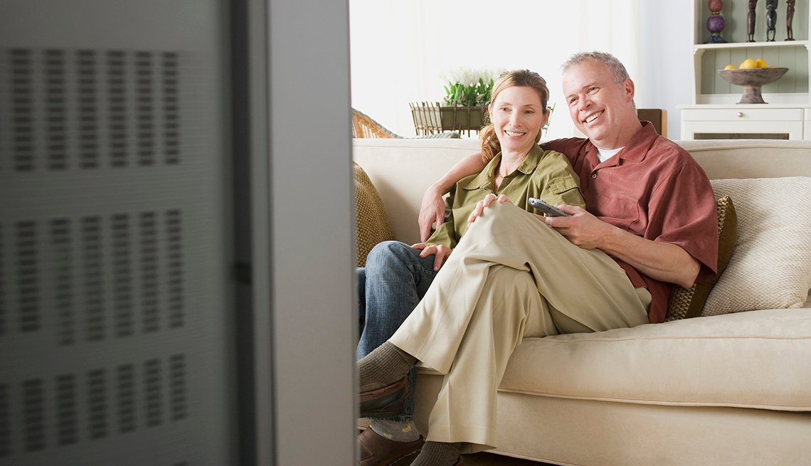 Couple on Couch, Television Foreground, Common Spending Regrets