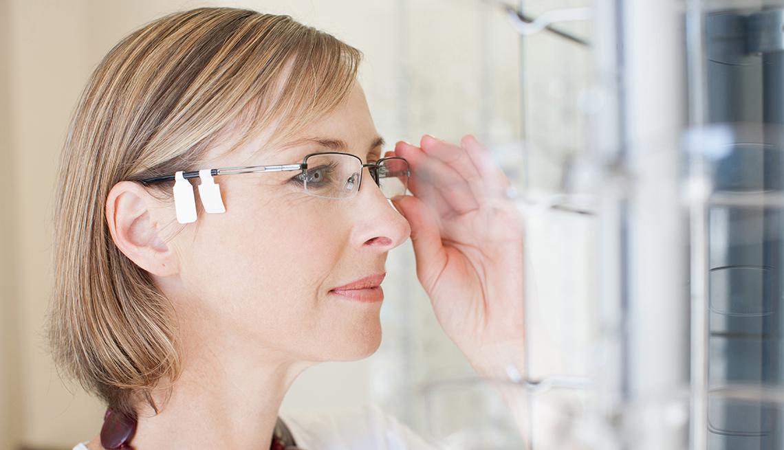 Mujer probándose unos lentes - Fomas de ahorrar dinero con cupones