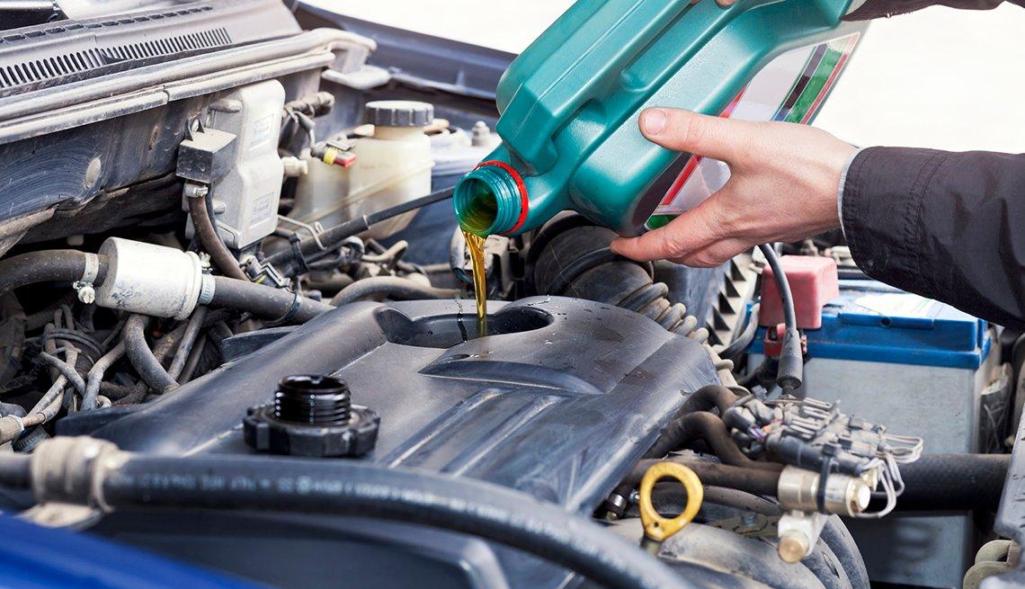 Un hombre colocando aceite al motor de un carro - Fomas de ahorrar dinero con cupones